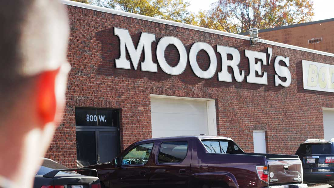 Customer looking at Moore's Body Shop building from parking lot